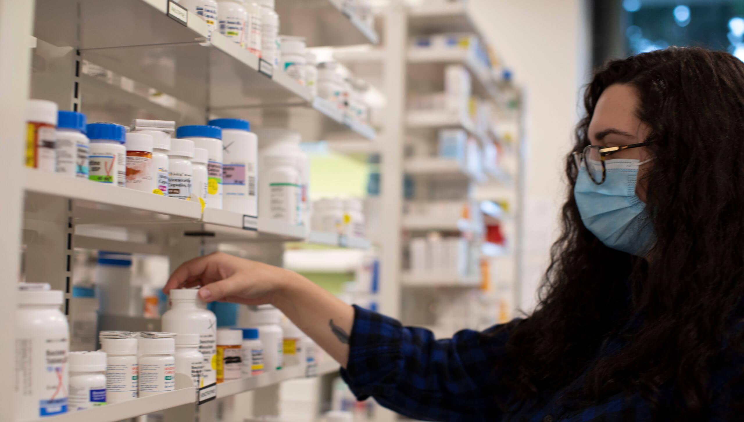 Pharmacy working grabbing a pill bottle