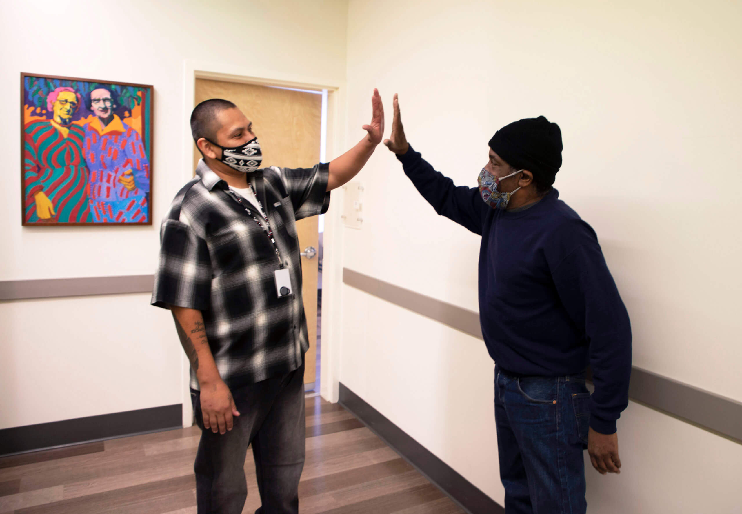 Two men giving each other a high-five inside Blackburn Center