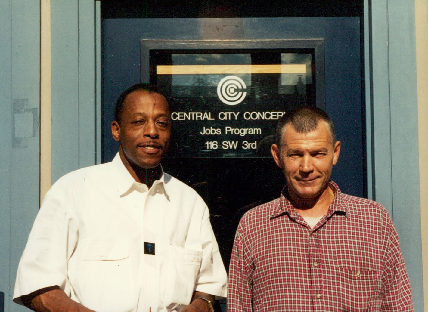 Two men standing in front of CCC jobs program sign in the 90s