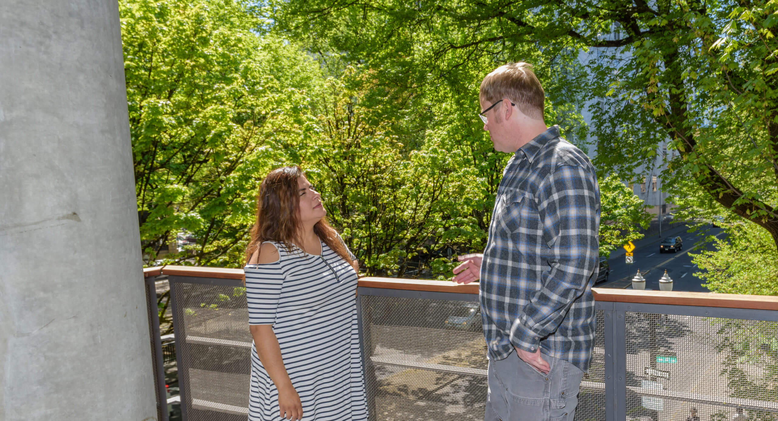 Two people standing on outside deck on sunny day