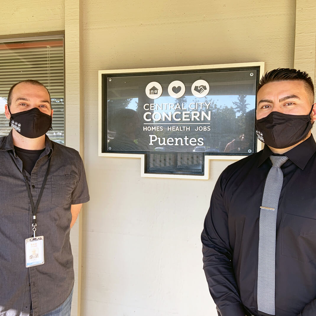 Two people posing outside in front of Central City Concern Puentes sign